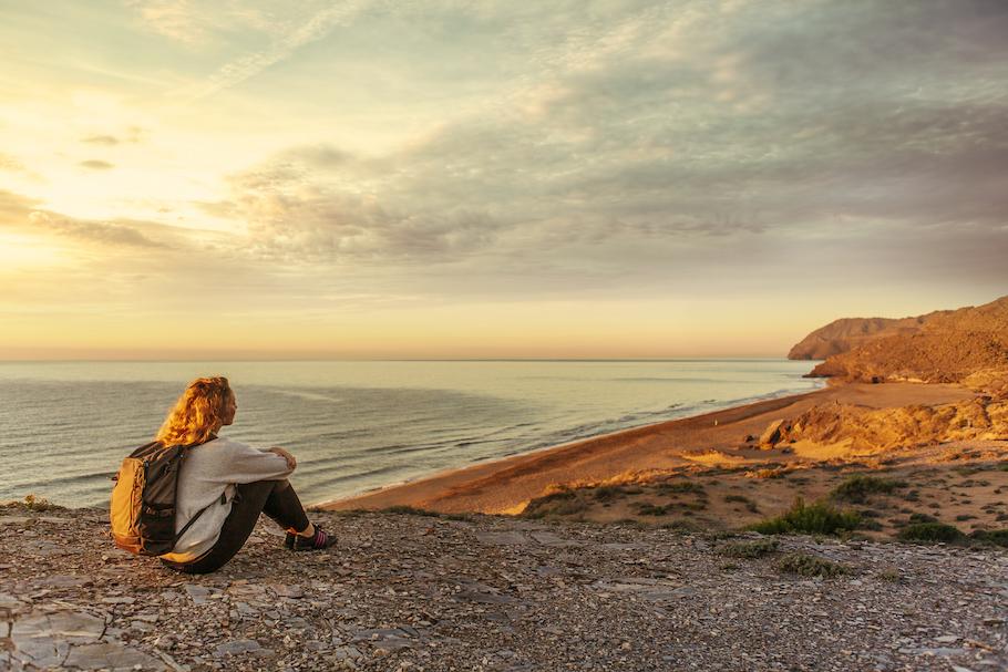 Woman meditating overlooking beach